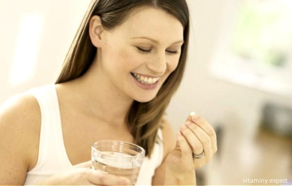 Женщина принимает фолиевую кислоту при планировании беременности