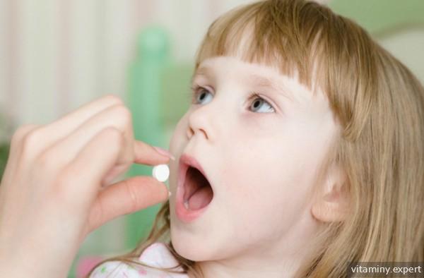 Девочка принимает витамины